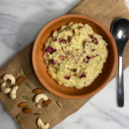 Rice pudding or Kheer in an earthenware bowl garnished with rose petals and crushed nuts on a white table with a spoon and nuts in the background
